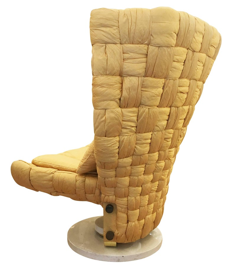 Swivel lounge chair designed by Marzio Cecchi in the 1970s. Upholstered in a woven gold silk. The base is lacquered white with brass details.  Condition: Excellent vintage condition, minor wear consistent with age and use.  Measures: Width
