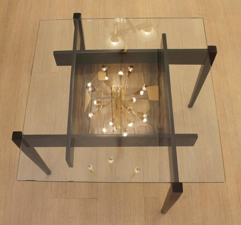Playful wood table with glass top. At the center there is a decorative cocktail themed etching.
