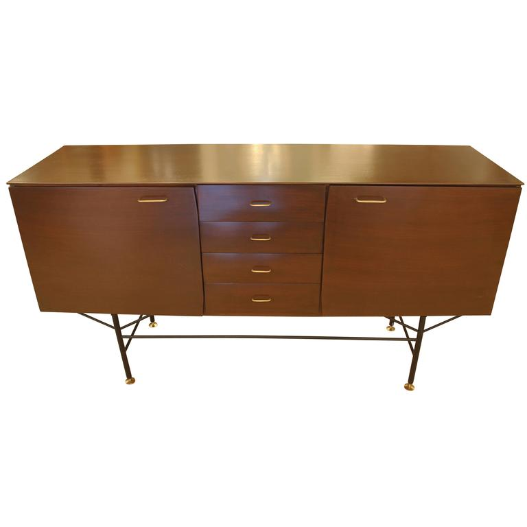 Exceptional Mid-Century Italian credenza made with a rosewood veneer. It has two large cabinets at the sides and four drawers at the center. The legs are black lacquered metal while the feet and handles are brass.