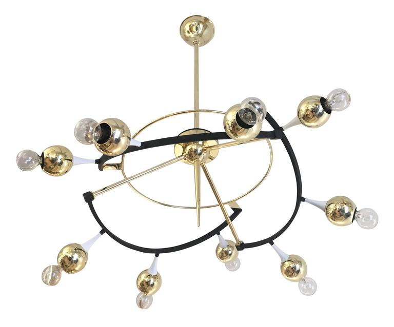 Exceptional orbital chandelier by Stilnovo featuring nine round brass shades. The elliptical frame is brass as well as lacquered white and black. Holds nine candelabra sockets.