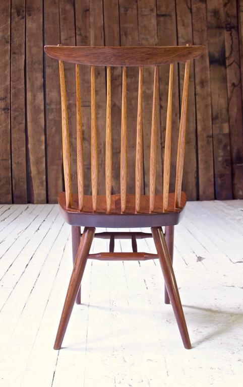 A well-preserved early 'New Chair' in black walnut and hickory, handmade by George Nakashima in his New Hope studio in the mid-late 1950s. Handplane and chisel marks are visible on the hand-hewn Hickory spindles, the turned leg stretchers' tenons
