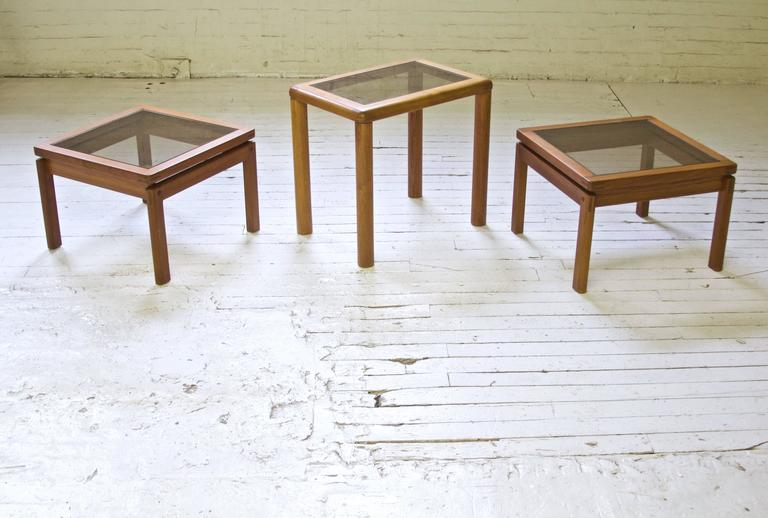 Set of three oiled teak occasional tables with exposed bridle joinery and smoked glass tops. Excellent construction, stamped made in Denmark.