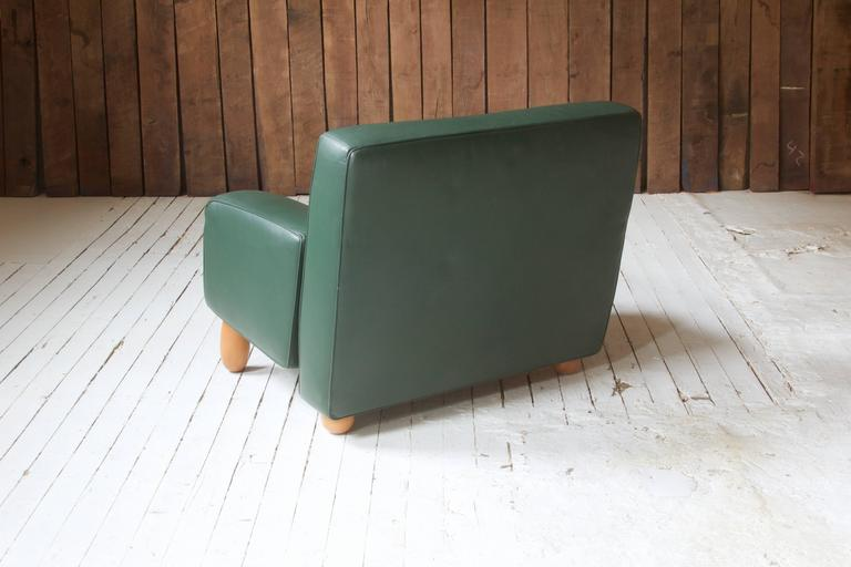 Commodious armchair with green leather upholstered frame and turned Beech wood feet by Moroso for Vitra Inc., circa 1994.