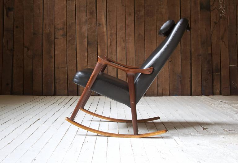 Attractive and comfortable teak and black vinyl rocking chair in original vintage condition by Ingmar Relling for Westnofa, Norway. This design features lovely sculpted arms and a removable counter-weighted headrest.