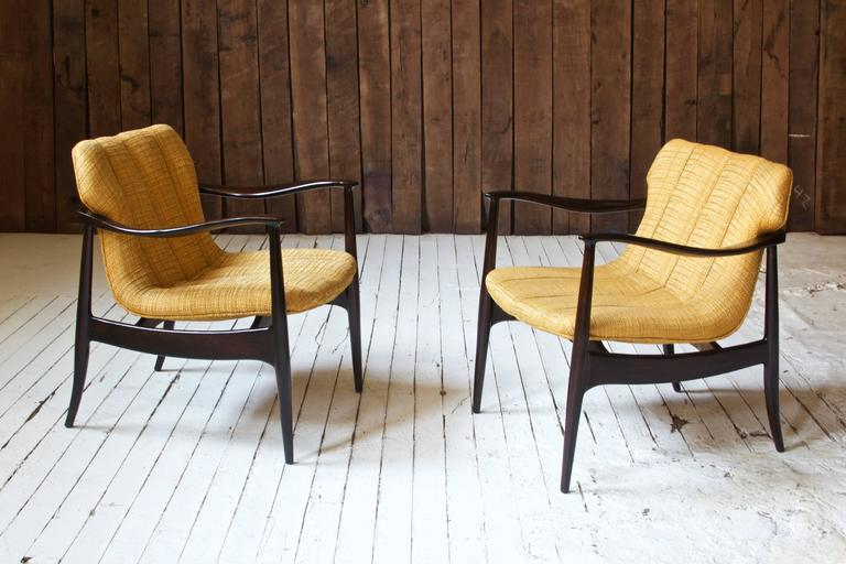 Stately pair of vintage Bertha Schaefer armchairs in polished black walnut with upholstered floating seat. Hand-carved continuous armrests cradle the shield shaped upholstered seat back; an elegant pair in excellent vintage condition.