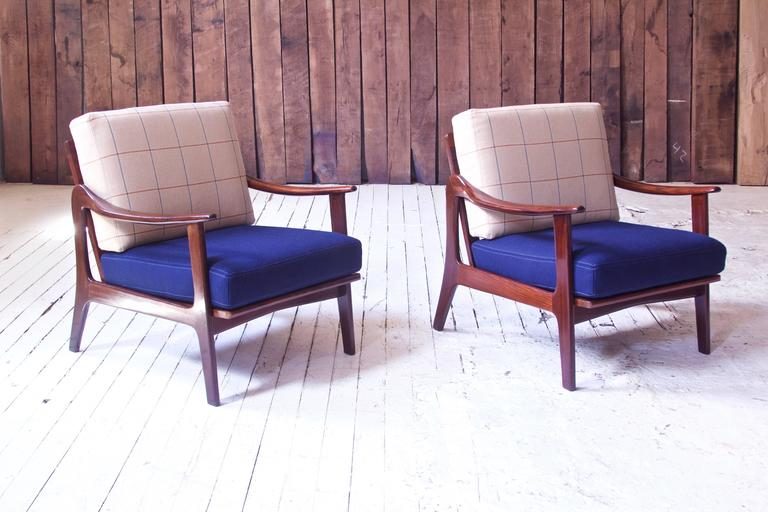Rare pair of sculpted teak lounge chairs by Norwegian-born furniture designer Fredrik A. Kayser; manufactured by Vatne Mobler in Norway, circa 1955. The chairs' cushions have been redone in royal blue and light plaid wool, frames reconditioned and