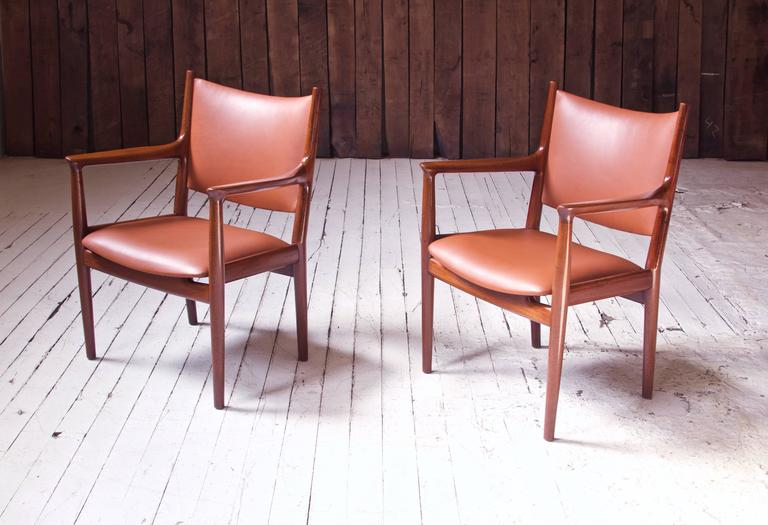 Handsome pair of vintage Hans Wegner for Johannes Hansen JH-513 teak and cognac leather conference chairs. Wegner's conference chairs of this period take inspiration directly from Designmuseum Danmark's own 18th century 'Spanish Travelling Chair',