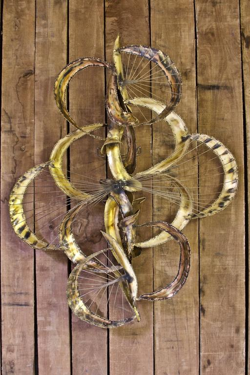 Stunning Brutalist wall sculpture in bent and welded torch-cut brass with thin brass 'spokes' spanning the crescent shapes. Incredible range of tones throughout the piece, certain sections of the brass alloy reveal more warm copper colors, while