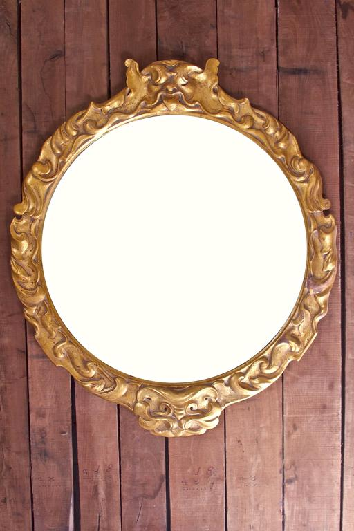 A lovely Italian Baroque Revival mirror in hand-carved giltwood with central gargoyle motif atop undulating scroll mouldings; this unique piece remains in original antique condition. With the exception of a few areas, most of the gilding remains on
