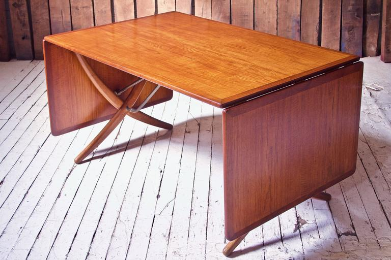 A gorgeous example of Wegner's lyrical AT-304 drop-leaf dining table in figured teak and white oak; complete with original brass hardware featuring an innovative tooth and pawl catch mechanism which allows both leaves to lock into place by simply