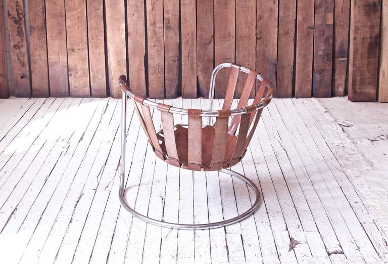 An interesting vintage French leather strapped sling chair, unique in design and surprisingly comfortable. The open, bent metal frame flexes and bounces to support the sitter in a weightless, completely suspended seat. Quality construction/leather