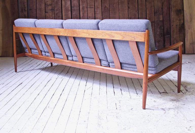 An excellent example of Grete Jalk's Classic FD-118 four-seat sofa in Teak and Italian grey boiled-wool; manufactured by France & Son, imported by John Stuart Inc. This expert, minimal frame design allows for lightness in appearance and strength in