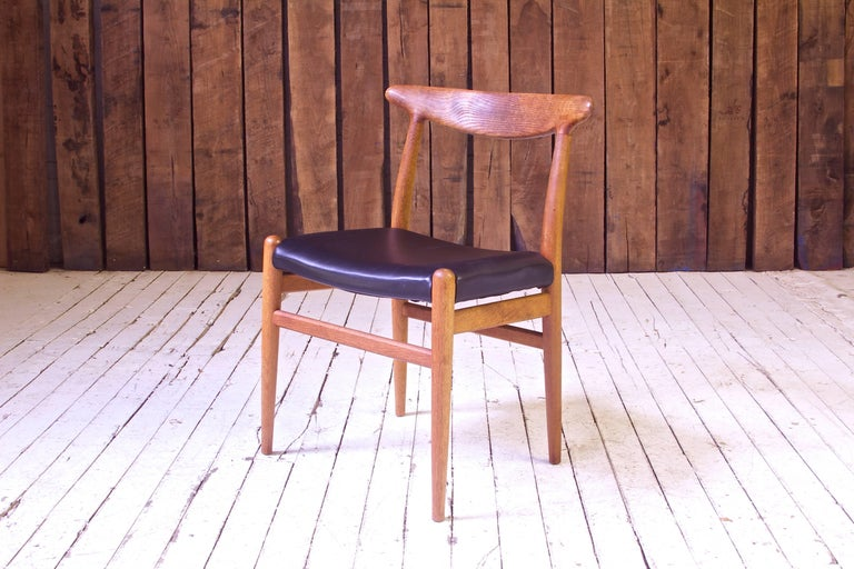 A lovely example of the early work of the 20th century's master of seating design, Hans J. Wegner. The sculpted oak backrest or top-rail employed here was developed as part of a family of innovative seating designs of the 1950s including Wegner's