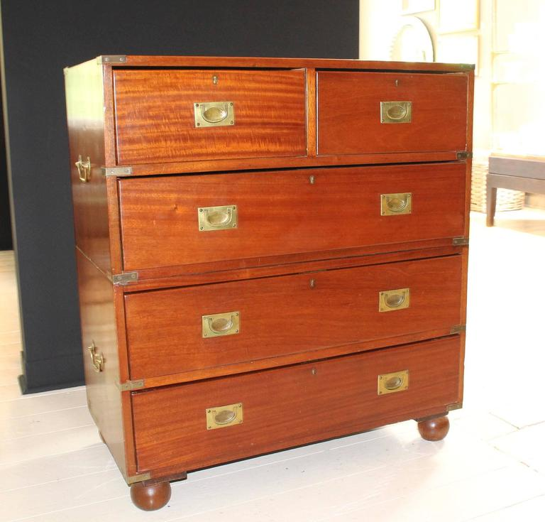 Five-drawer Campaign chest, 19th century England, in two parts on bun feet with recessed brass drawer pulls and corner hardware.