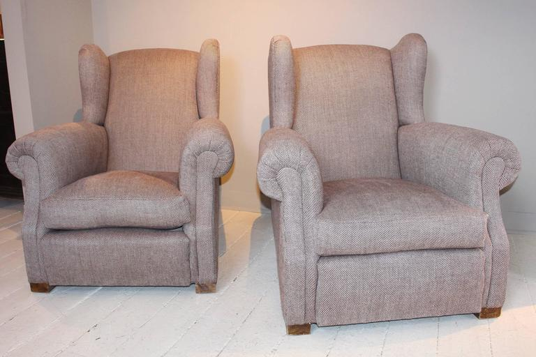 Pair of wingback club chairs, 1920s, France. With impressive scale and well-cushioned armrests. Raised on block feet, the chairs are newly upholstered in a Rogers & Goffigon brown twill fabric.