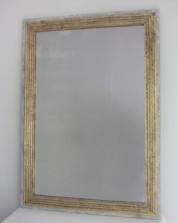 19th century Directoire style rectangular mirror with fluted giltwood surround mounted on painted base, with later gilt and paint.
