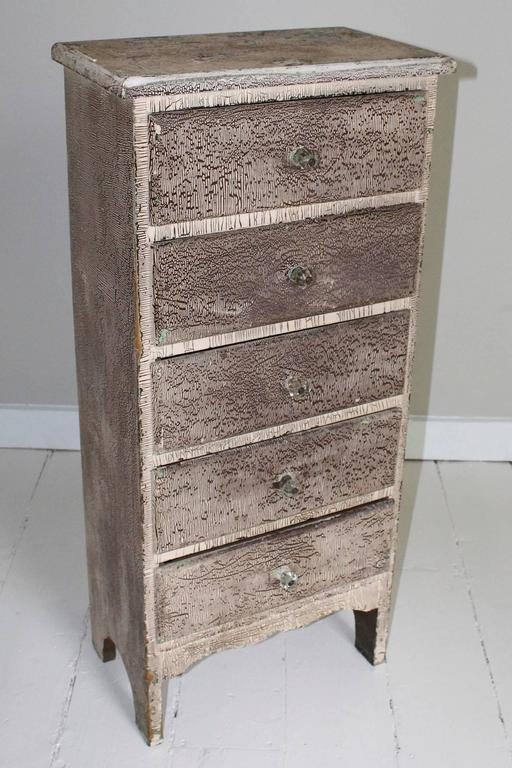 Vintage attic chest of drawers, 1960s USA, with narrow profile, in later crackled paint to front and sides, distressed paint top, green painted plank back. Drawers have glass knobs.