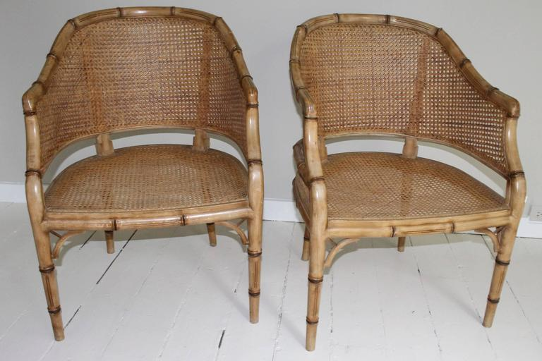 Pair of vintage French faux bamboo wood armchairs with Classic chinoiserie details, circa 1940s, with tub shaped backs, cane seats and backrest. Cushions included will need recovering.