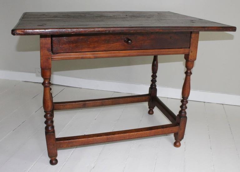 Refined 18th century American oak tavern table on turned wood legs joined by stretcher supporting a broad plank top with wonderful time-worn patina. Single drawer distinguished by Novel Elongated Pull.