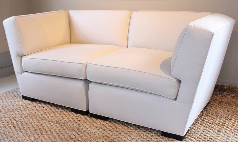 Donghia loveseat with angular armrests newly upholstered in a Rogers & Goffigon cotton. United by interlocking connecting hardware, the sections disconnect to be used as individual chairs.