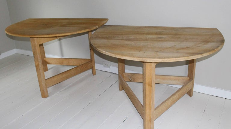 Pair of similar modern demilune tables in bleached maple with removable top hand-crafted of boards supported by three angular legs with stretchers. One table measures 45.5