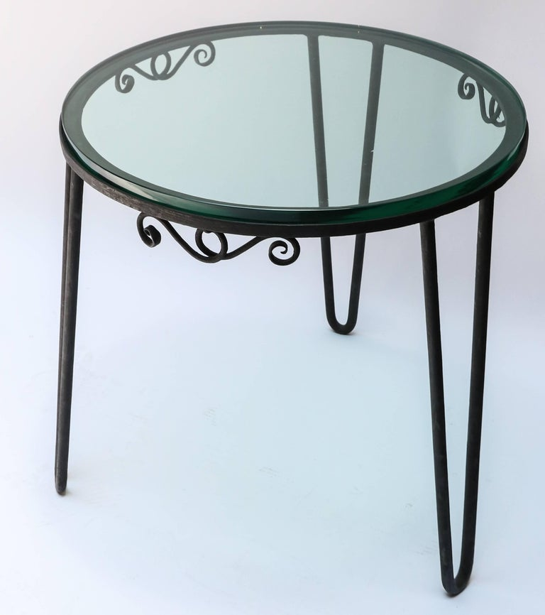Round black metal Italian side table from the 1960s with thick glass top.