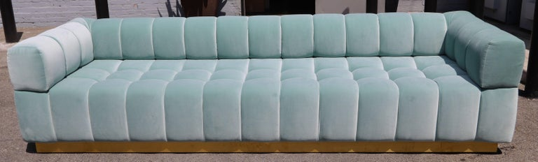 Custom tufted sofa with brass base, in aqua blue velvet. Can be made in different colors and fabrics or a different metal for the base.