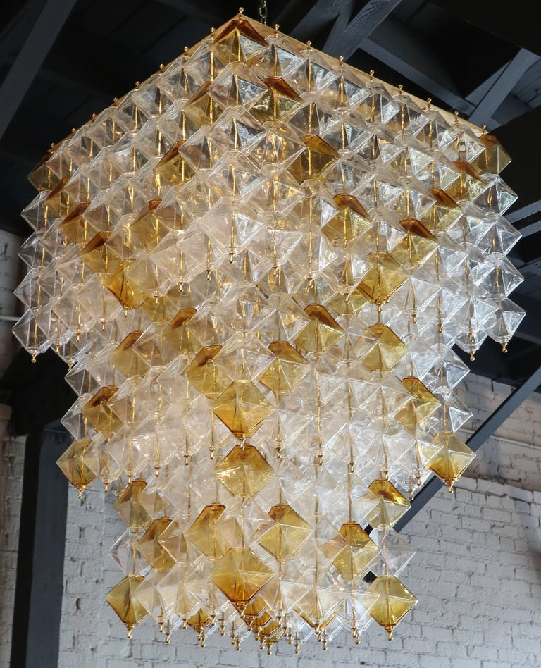 Tiered chandelier from the 1970s with clear and orange Murano glass pieces on a brass frame.