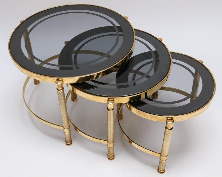 "Set of three brass nesting tables with decorative details and smoked glass tops.  Small:  14.75"" dia x 11.75"" high Medium:  17.5"" dia x 13"" high Large:  20.25"" dia x 14.25"" high"