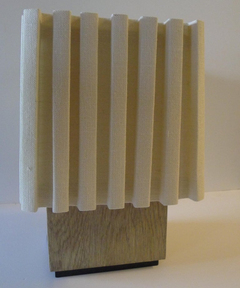 Paul Marra modern distressed oak lamp. Natural oak in grey beige, color will vary dependent on the natural light. With heavy box pleated linen shade. (See listing of other version in silver distressed.) Base 10 x 10 x 9.25 H, overall measurements