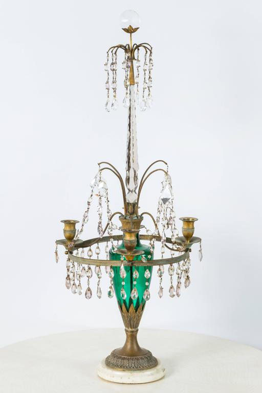 Pair of neoclassical gilt bronze girandole candelabra, late 19th century Gustavian Swedish style or Baltic Empire style. Emerald green baluster-form shaft. There has been much restoration including some of the crystal cut-glass. Marble base.