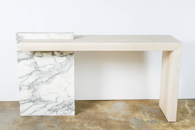 Contemporary Carrara Marble and Bleached Oak Console. By order.  Dimensions provided are overall 61.75 W × 34 H x 16 D inches; the oak top is 59.25 W x 32 H x 16 D inches.