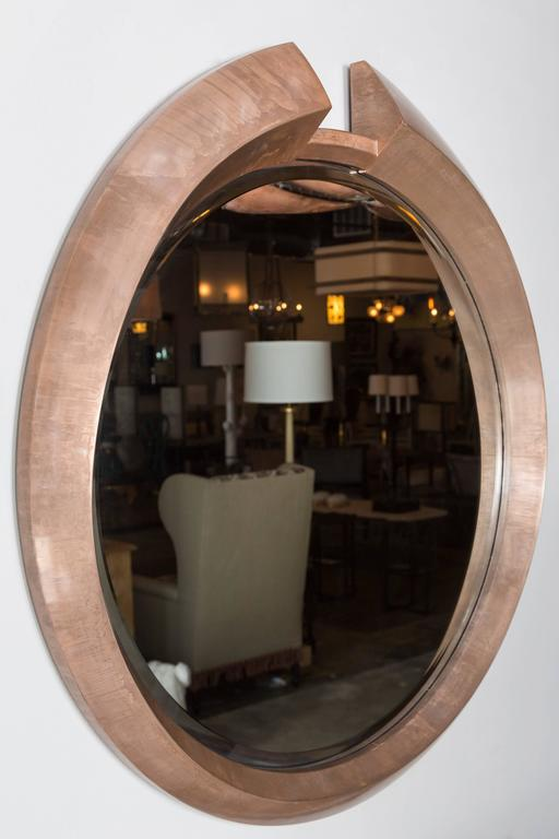 Large round modern architectural, split pediment mirror in a light bronze finish over wood. The finish results as if the frame is made of metal. By order.
