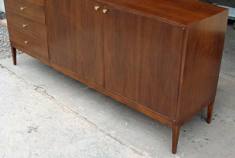 Gorgeous 12-Drawer designed by Paul McCobb for Calvin. Walnut cabinet with original brass pulls.  Restored finish.  The bank of drawers on left side features pop-up vanity mirror. To right are double bi-fold doors with 8 pull-out drawers behind.