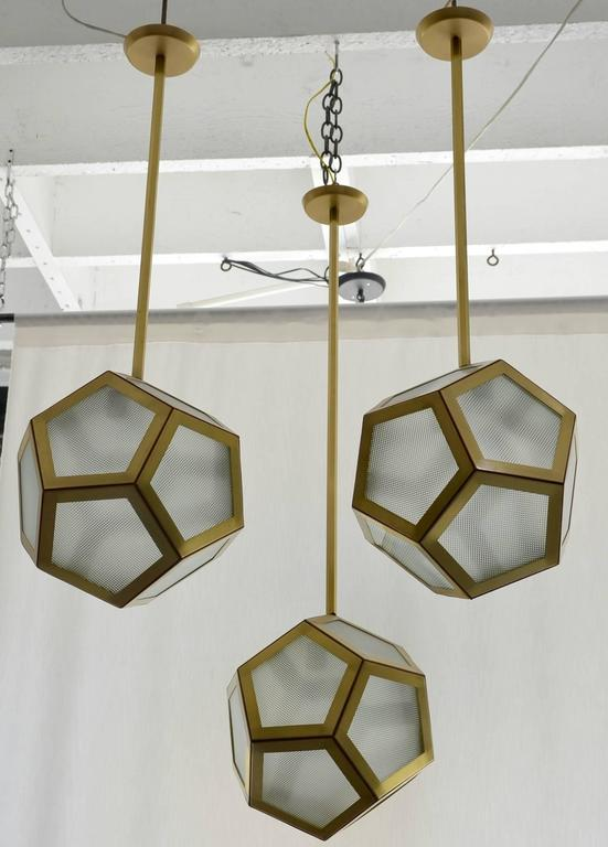 Large cluster chandelier of three pentagon lanterns by Design Frères. Rods can be adjusted at different lengths to create a layered effect. Also sold individually.