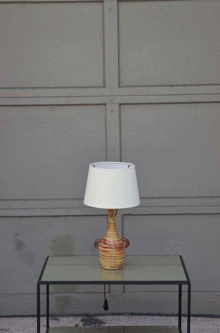 Chic French Gourd-shaped glazed ceramic lamp by Accolay Pottery, France. New custom cream European-style parchment shade included. The shade itself is 8 in. diameter at top x 10 in. diameter at bottom x 7 in. tall.  The History of Accolay