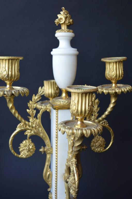Detailed marble French clock set embellished with gilded bronze.