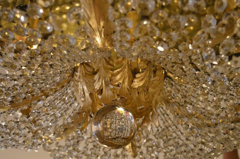 Set of four grand Hollywood Regency flush mount chandeliers. Ornaments are gold leafed.