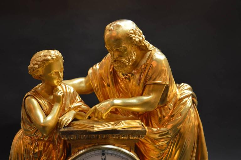 French doré bronze and white marble clock with figures of a scholar with a young student.