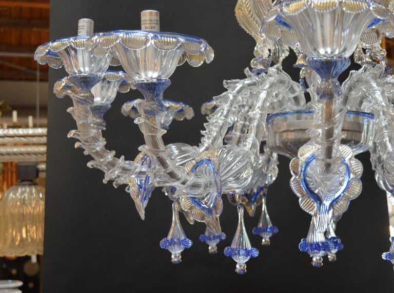 This is a pair of wonderful Murano handmade in Italy chandeliers with a wonderful detail and design in excellent working condition. Blue details with gold flecks.