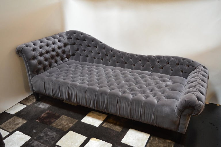 Deep grey tufted chaise longue.