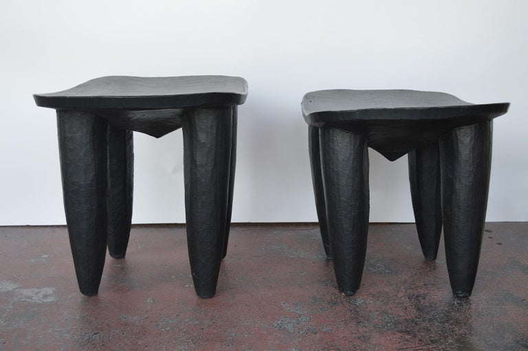 Two hand-carved wood side tables or stools, painted black.
