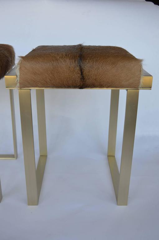 Pair of brushed brass stools upholstered in cowhide.
