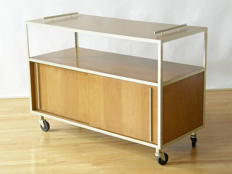 Utilitarian, late 1950s serving cart with a laminated top surface for protection against spillage, an open shelf below that and a large, closed storage area in the bottom section with sliding doors.