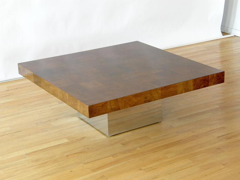 Square coffee table with walnut patchwork veneer top and chrome clad cube base designed by Milo Baughman.