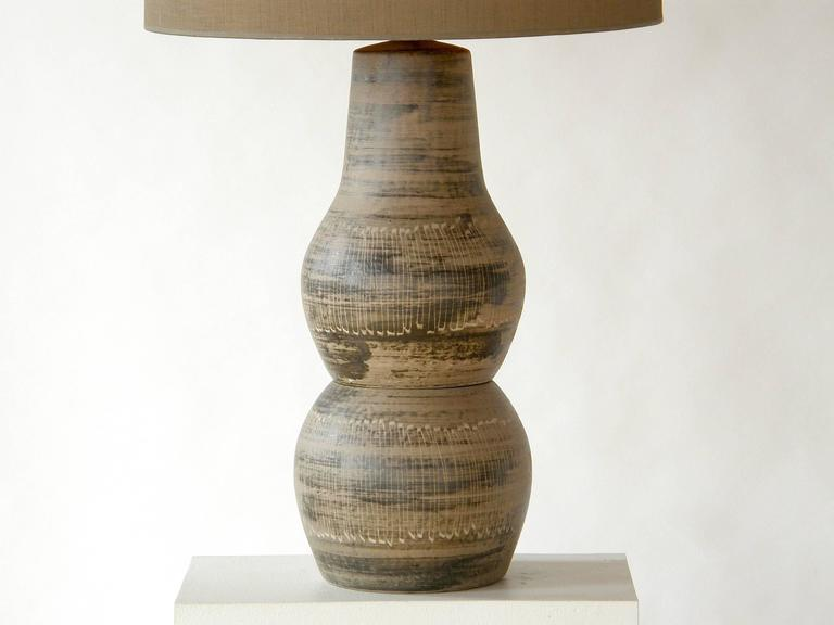 Ceramic table lamp with incised decoration and original turned wood finial by Jane and Gordon Martz. This design is shown in their 1955 catalog.