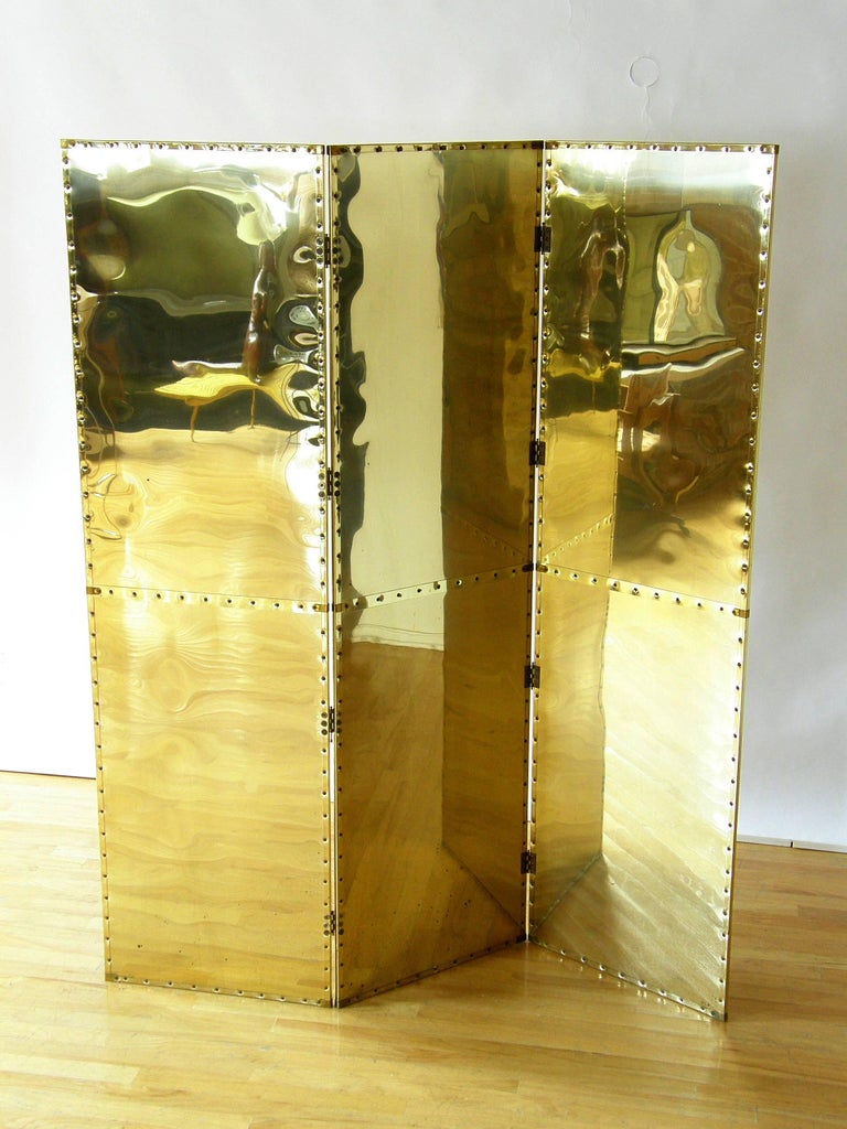 """This brass clad folding screen or room divider in the style of Sarreid has three panels with riveted trim. The measurements given are for the screen fully extended flat without any angles. Each panel is 20"""" wide.  Please contact us if you"""