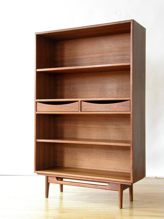 This is a great storage cabinet with a fairly small footprint. It has two adjustable shelves to hold books or display decorative objects and two small drawers for hidden storage. The sculptural base and the cut out drawer fronts add a whimsical