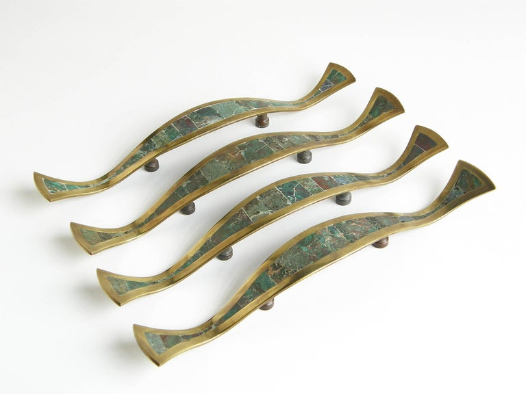 Set of four handmade door or drawer pulls from the Los Castillo workshop in Taxco, Mexico. They are sinuous in form with elegantly curved edges and profiles. 