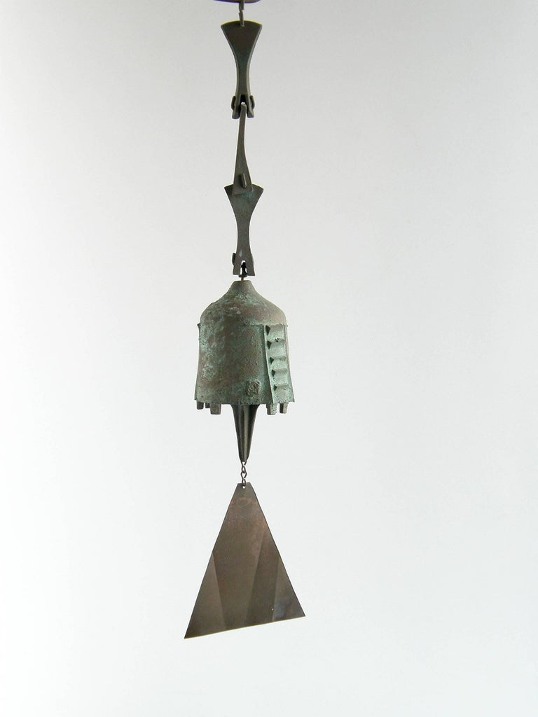 Sand cast bronze wind chime bell by Paolo Soleri. It hangs from a three link chain and has a triangular tail hanging from the clapper to catch the wind.